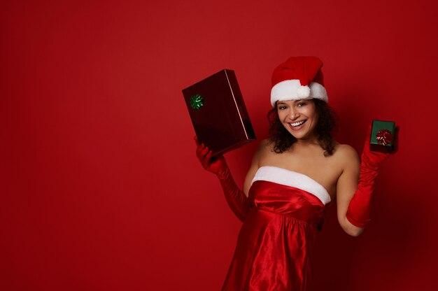 산타 카니발 복장을 한 매력적인 아름다운 여성은 녹색 및 빨간색 포장지로 크리스마스 선물 상자를 들고 광고를 위한 복사 공간이 있는 컬러 배경에 대해 포즈를 취하는 카메라에 미소를 지으며 기뻐합니다.