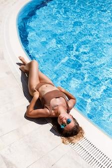 갈색 수영복을 입고 수영장 옆에서 휴식을 취하는 비키니를 입은 금발 머리를 가진 매력적인 아름다운 여성, 거짓말과 휴식