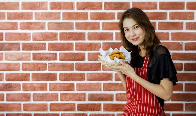 붉은 줄무늬 앞치마를 입은 매력적인 젊은 아시아 여성이 벽돌 벽 근처에 서서 튀긴 스낵과 쟁반을 입 가까이로 올려 좋아하는 맛있는 음식을 먹도록 미소를 지으며 설득합니다.