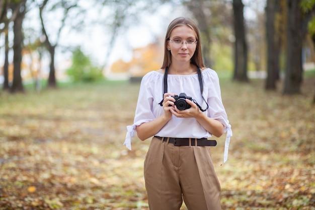 가을 공원에서 현대 미러리스 카메라를 들고 매력적인 아름다운 어린 소녀