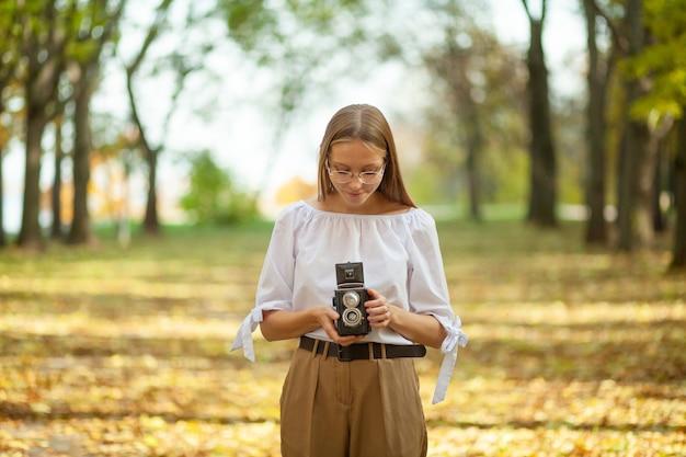 秋の公園でレトロなビンテージ二眼レフ反射カメラを保持している魅力的な美しい少女