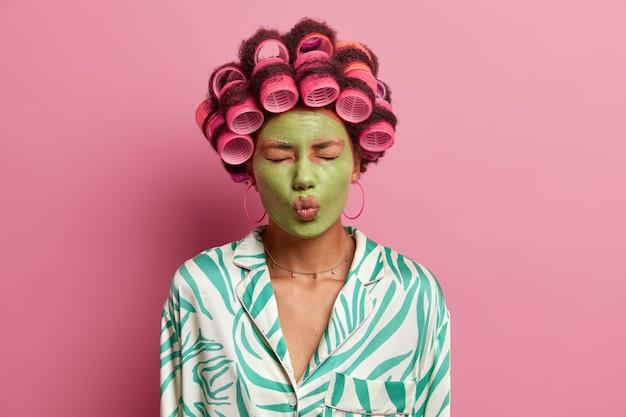 Attraente bella giovane donna chiude gli occhi, mantiene le labbra arrotondate, applica una maschera idratante verde sul viso, indossa i bigodini, si prepara per un'occasione speciale, indossa la vestaglia