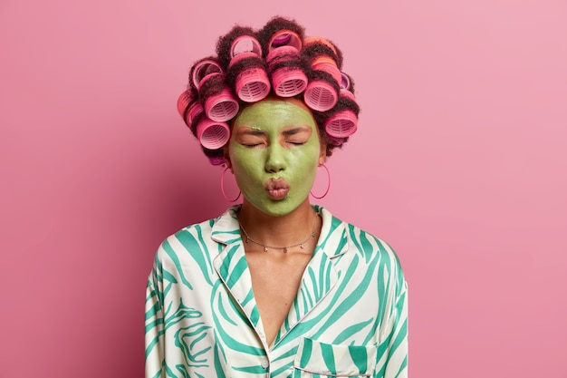 매력적인 아름다운 젊은 여성이 눈을 감고, 입술을 둥글게 유지하고, 얼굴에 녹색 보습 마스크를 바르고, 헤어 컬러를 착용하고, 특별한 날을 위해 준비하고, 드레싱 가운을 입습니다.