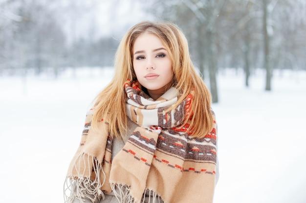 겨울 눈 덮인 숲에서 세련 된 따뜻한 겉옷에 매력적인 아름 다운 젊은 여자. 귀여운 소녀.