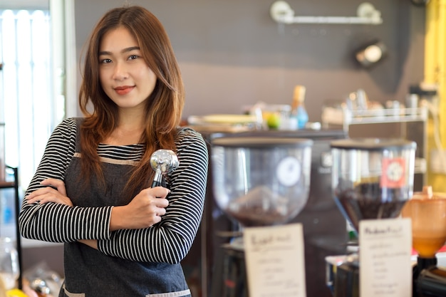 カウンターの前に立って、portafilterを保持している魅力的な美しさのアジアの女性バリスタ