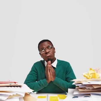 Attraente uomo di colore tiene le mani nel gesto di preghiera, prega mentre lavora al desktop, indossa occhiali trasparenti, guarda con espressione di pietà