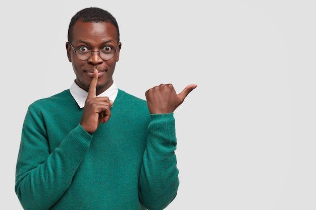 매력적인 흑인 남자는 쉿 취하고 조용하고 조용해야하며 엄지 손가락으로 옆으로 표시하고 빈 복사본 공간에서 보여주고 공식적인 옷을 입습니다.
