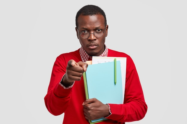Привлекательный темнокожий мужчина с серьезным выражением лица, указывает указательным пальцем, несет книгу и другие необходимые документы для работы над проектом