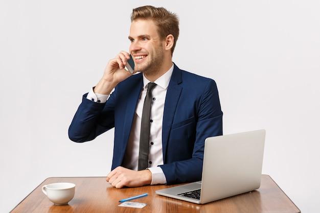 Привлекательный белокурый бородатый бизнесмен в офисе разговаривает по телефону