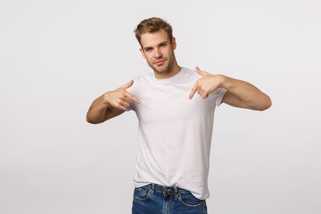 Attractive blond bearded man in white t-shirt pointing himself