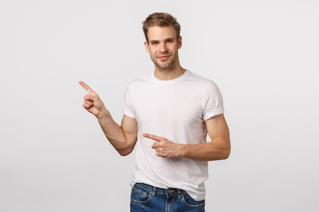 Attractive blond bearded man in white t-shirt pointing to the side