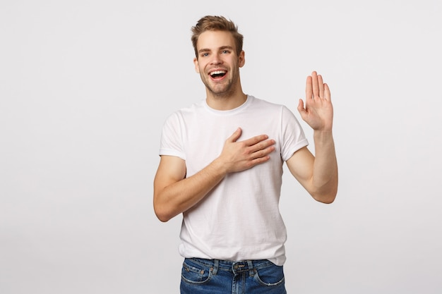 Attractive blond bearded man in white t-shirt raises one hand and holds another on heart