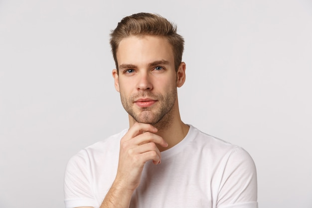 Attractive blond bearded man in white t-shirt thinking