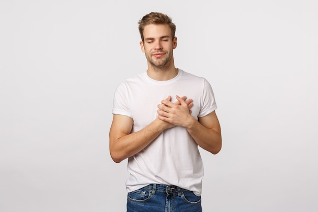 Attractive blond bearded man in white t-shirt with hands on heart