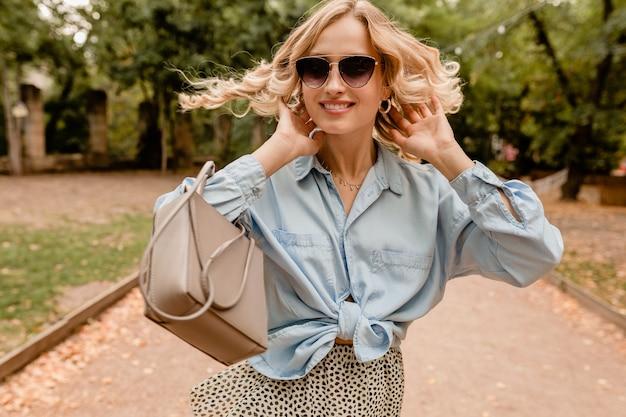 Привлекательная белокурая откровенная женщина гуляет в парке в стильном наряде в элегантных солнцезащитных очках и сумочке