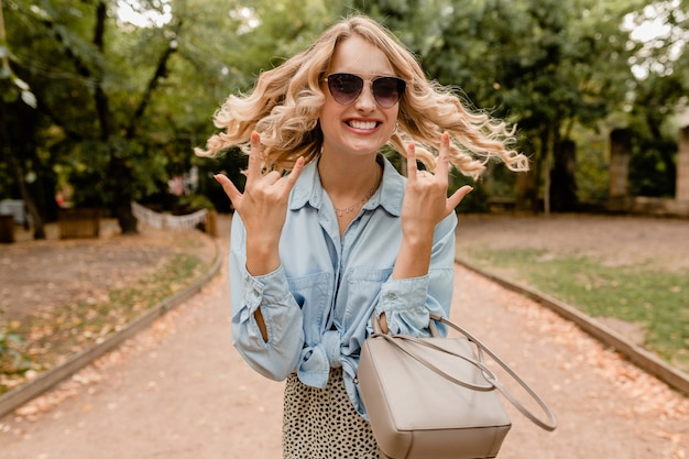 Attractive blond candid woman walking in park in stylish outfit wearing elegant sunglasses and purse