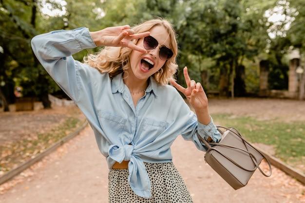 Attraente bionda candida donna che cammina nel parco in abito estivo indossando occhiali da sole eleganti e borsa