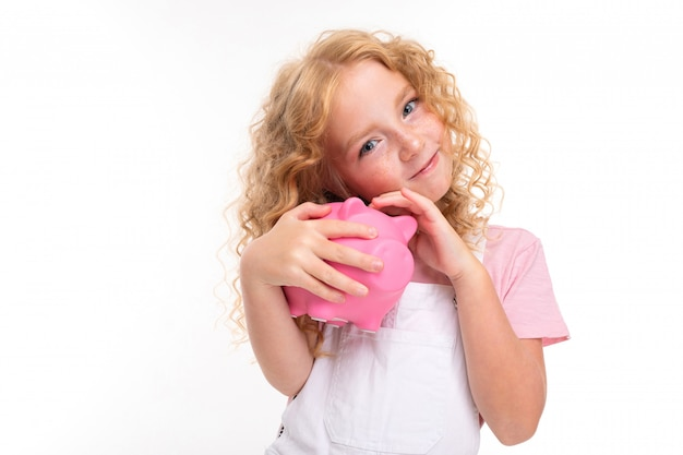 Attractive blond curly girl holding a piggy bank in her hands on light blue