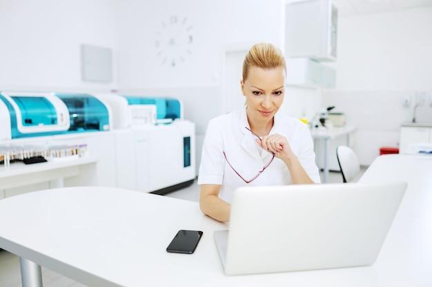 ラボに座ってラップトップを使用してテスト結果を入力する魅力的な金髪の女性ラボアシスタント。