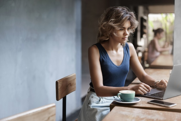 Attractive blond girl freelancer working laptop taking notes notebook sit alone cafe near window drink coffee, professional writer make post online blog, prepare files business meeting after lunch.