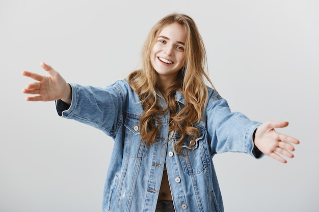 Attractive blond girl smiling happy and spread hands sideways for hug, embracing or taking something