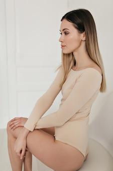 白いアパートに座っているベージュのボディを身に着けている魅力的なブロンドの女の子。壮大な白人女性の室内写真