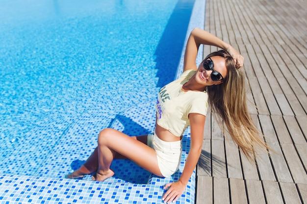 Привлекательная блондинка с длинными волосами сидит возле бассейна. она позирует и улыбается. горизонтальный вид сверху.