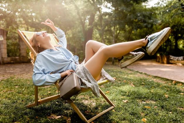 Attraente donna bionda felice seduta rilassante sulla sedia a sdraio in camicia blu vestito estivo, indossando scarpe da ginnastica d'argento, occhiali da sole eleganti e borsa