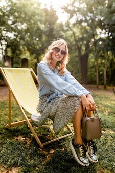 Attraente donna bionda felice seduta rilassante in sedia a sdraio in abito estivo