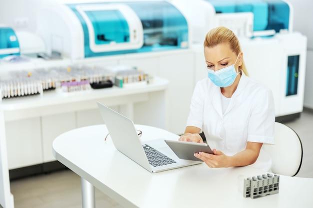 Привлекательный белокурый лаборант в пальто со стерильной хирургической маской сидит в лаборатории