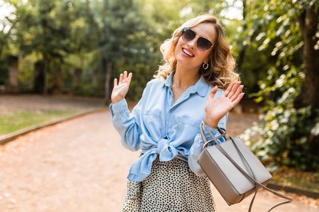 エレガントなサングラスと財布を身に着けているスタイリッシュな衣装の青いシャツを着て公園を歩いている魅力的な金髪の笑う率直な女性