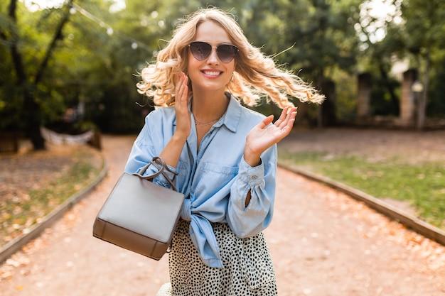 Donna candida che ride bionda attraente che cammina nel parco in camicia blu vestito alla moda indossando occhiali da sole eleganti e borsa