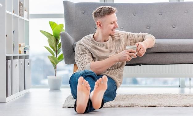 Привлекательный белокурый мужчина сидит на ковре, держа в руках чашку чая и кофе и улыбается