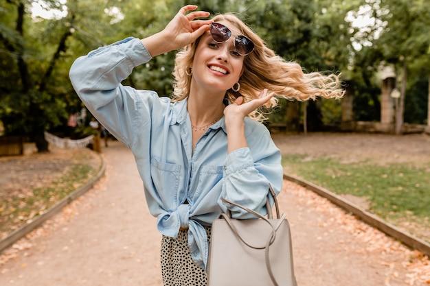 Привлекательная белокурая улыбающаяся откровенная женщина гуляет в парке в летнем наряде в элегантных солнцезащитных очках и кошельке