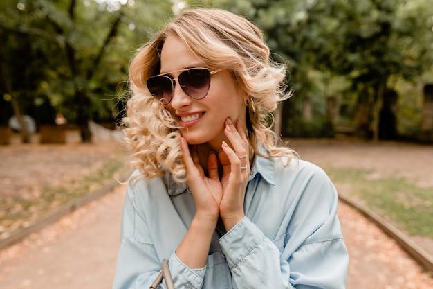 Привлекательная белокурая улыбающаяся откровенная женщина гуляет в парке в летнем наряде