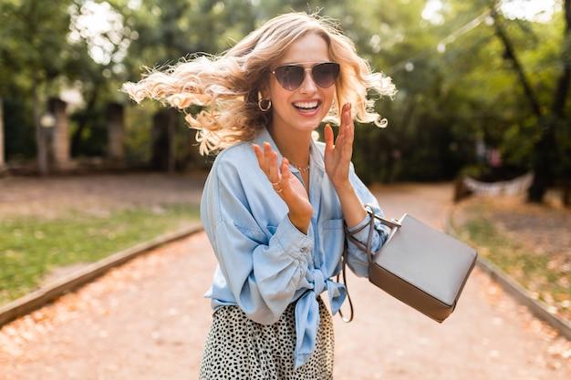 Attraente bionda sorridente candida donna che cammina nel parco in camicia blu vestito estivo, indossando occhiali da sole eleganti