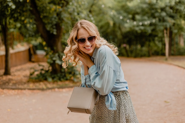 Attractive blond smiling candid woman walking in park in summer outfit