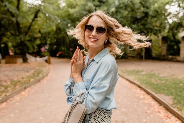 Attraente bionda sorridente candida donna che cammina nel parco in abito estivo