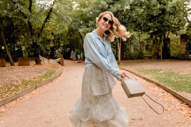 夏の服装で公園を歩いて楽しんで長い髪を振って魅力的な金髪笑顔率直な女性