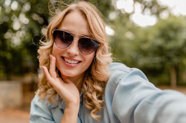 Привлекательная белокурая улыбающаяся женщина с белыми зубами гуляет в парке в летнем наряде, делающем селфи на телефоне