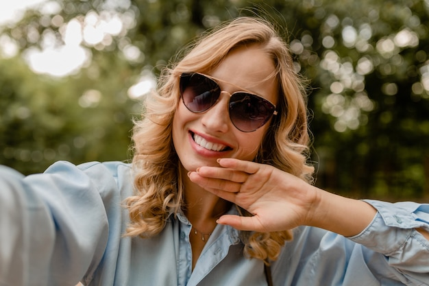 Attractive blond smiling white teeth woman walking in park in summer outfit taking selfie photo on phone