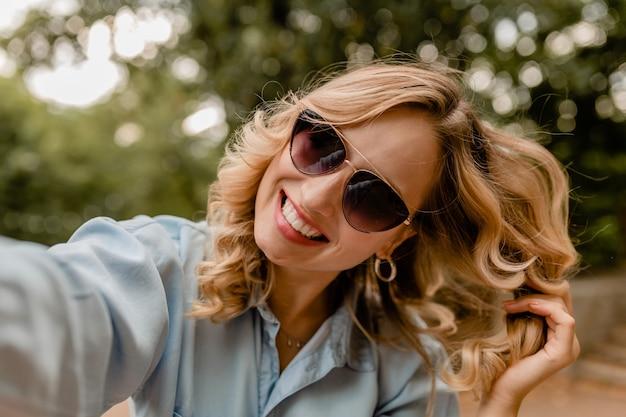 Donna bionda sorridente attraente dei denti bianchi che cammina nel parco in vestito di estate che prende la foto del selfie sul telefono