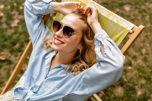 Attraente donna bionda sorridente seduto sulla sedia a sdraio in abito estivo