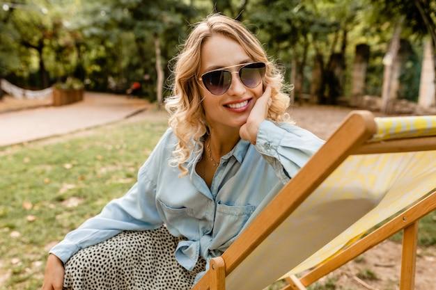 Привлекательная белокурая улыбающаяся женщина, сидящая в шезлонге в стильном наряде