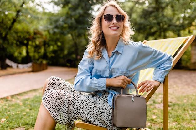 スタイリッシュな衣装でデッキチェアに座っている魅力的な金髪の笑顔の女性