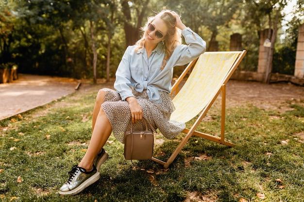 夏の衣装の青いシャツとスカートのデッキチェアに座って、銀のスニーカー、エレガントなサングラスと財布、ストリートファッションスタイルを身に着けている魅力的な金髪の笑顔の女性