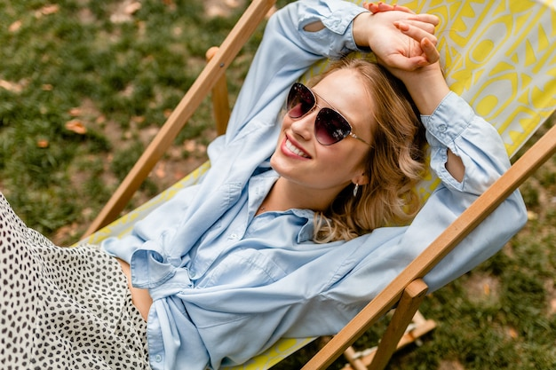 여름 옷에 갑판 의자에 앉아 매력적인 금발 웃는 여자