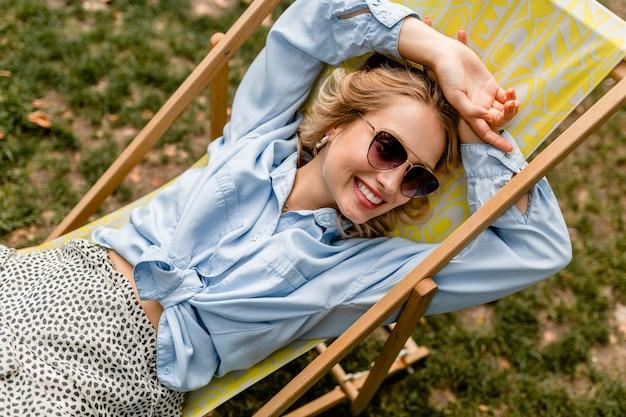 Привлекательная белокурая улыбающаяся женщина, сидящая в шезлонге в летнем наряде