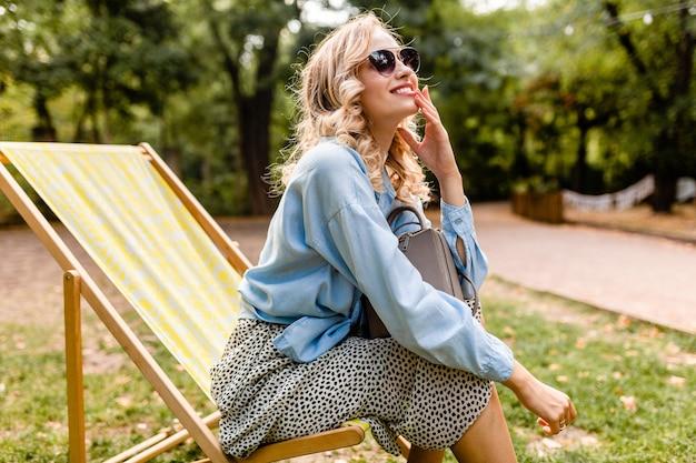 夏の衣装でデッキチェアに座っている魅力的な金髪の笑顔の女性