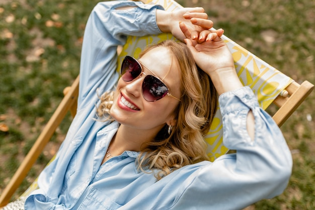 Attraente donna bionda sorridente seduto rilassato in sedia a sdraio in abito elegante